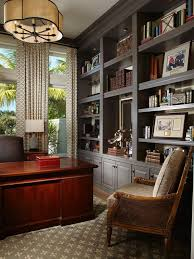 with a glossy mahogany desk and expansive gray built ins this home office exudes artistic home office track