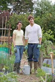 Man and woman in <b>gardening gloves with</b> watering can in front of ...