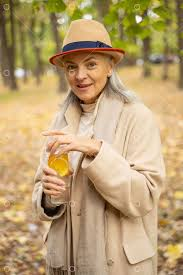 Pleased <b>stylish woman</b> opening a sports bottle in a park Image ...
