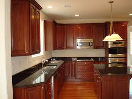 kitchen cabinets with granite countertops: redbrown color of cabinetry with island also pendant lamp also wooden laminating flooring also recessed lighting kitchen
