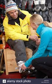 s assistant helping man to try on ski boots in hire shop stock s assistant helping man to try on ski boots in hire shop