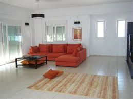 contemporary greek living room in white and cream with a sofa in burnt orange burnt orange living room furniture