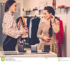 shop assistant at a clothes store royalty stock images w choosing clothes shop assistant stock photo