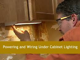 a white man leaning over a kitchen cabinet holding a light cabinet lighting guide sebring