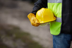 construction jobs are not affected by the economic crisis in uk builder yellow helmet and working gloves on building site