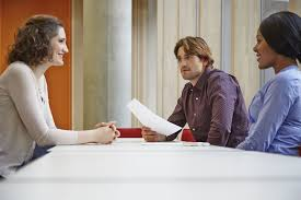 job interview questions and answers a man and w interviewing a candidate at a table
