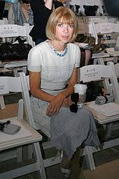 a seated woman wearing a white dress holding a coffee cup and sunglasses looking anna wintour office google