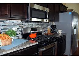 kitchen backsplash stainless steel tiles: granite countertops glass amp stone backsplash tile and stainless steel appliances brighten up dark birch cabinetry