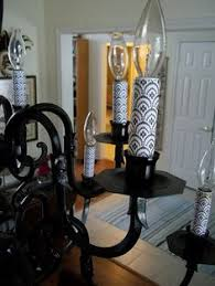 a spray painted old brass light fixture with scrapbook paper added to the candles awesome idea amelie distressed chandelier perfect lighting