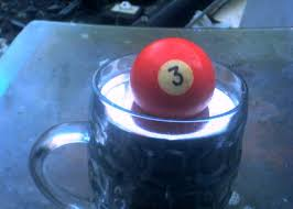 A pool ball floating in a cup of liquid Mercury.