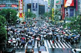 Photograph Crowds of people cross a street in a busy Japanese city  Japan has