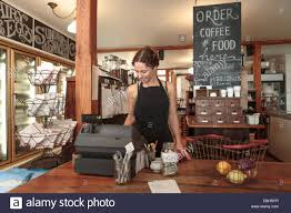 female s assistant using check out till in country store cafe female s assistant using check out till in country store cafe