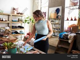 female shop assistant arranging a clothes shop display stock photo female shop assistant arranging a clothes shop display