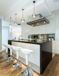 black appliance matte seamless kitchen: polished modern kitchen with gloss white cabinets and black counter