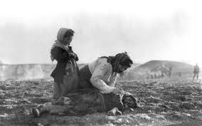 n genocide an n w kneeling beside a dead child in field in sight of help and safety at aleppo