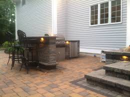 patio outdoor stone kitchen bar: outdoor landscape lighting illuminates a natural stone outdoor kitchen by bahler brothers in cromwell ct