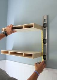 measuring for placement of a second floating shelf in a diy floating shelves project build floating shelves