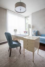beautiful home office desin with white desk and rounded chandelier and blue chair at memorial park blue white home office