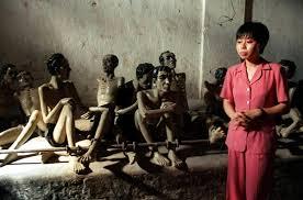 Die Museumsführerin Phung Thi Huong sitzt auf einem der berüchtigten - phung-thi-huong-leitet-besucher-durch-das-gefaengnis-in-dem-insgesamt-rund-80-figuren-die-bedingungen-der-gefaengnisinsassen-nachstellen-sollen-