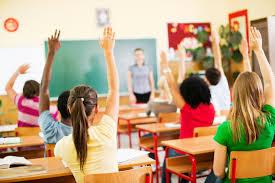 Children raising hands in a classroom