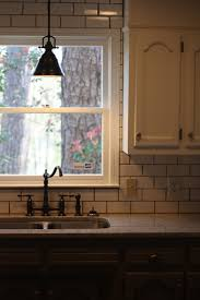 classic pendant lamp as kitchen sink light fixture white subway tiles backsplash a glass window with above kitchen sink lighting
