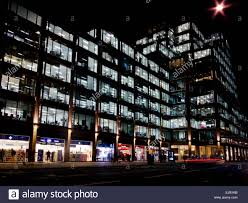 brightly lit shops and office building at night in victoria street in westminster central london england uk brightly colored offices central st