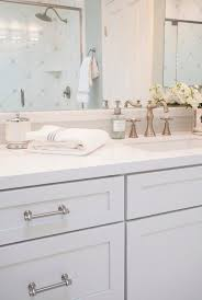 bathroom features gray shaker vanity: lovely bathroom features white shaker vanity cabinets adorned with stain nickel pulls paired with white quartz and a linear gray glass tiled backsplash