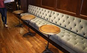 which was set with plush button tufted banquettes antique furnishings and lighting fixtures a gorgeous brass bar top and custom built leather stools bar top lighting