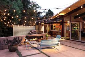 attach string lights to exteriors and left them hang freely over an open space backyard string lighting