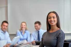 college day jan for business careers news and events an image of a smiling women in the foreground of a business meeting