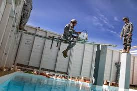 u s department of defense photo essay a ier carefully moves an ammo can across the water obstacle at the confidence course during