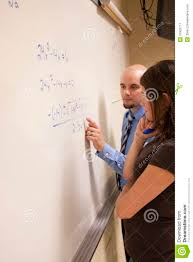 teacher helping student a math problem on a whiteboard teacher helping student a math problem on a whiteboard