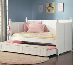 white stained wooden trundle day bed with side board placed on brown stained wooden floor as bedroom endearing rod iron