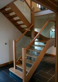 half turn staircase with a lateral stringer wooden frame and glass steps broadleaf bespoke glass staircase