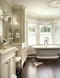 bathroom features gray shaker vanity: lovely bathroom for two with gray walls paint color freestanding tub in front of bay windows twin white bathroom vanities with marble countertops flanking