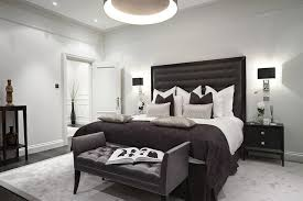 chelsea town house example of a transitional bedroom design in london with white walls and dark black grey white bedroom