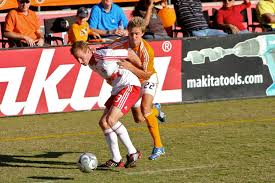 the red hunting hat used as a symbol in catcher in the rye by stuart holden of houston dynamo right vs chris leitch of red bull new york