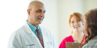 foot and ankle wellness centre dr chaudhry and an employee greeting a female patient the doctor is wearing a