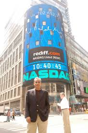 Ajit Balakrishnan, founder and CEO of Rediff.com with his signature on the Nasdaq tower behind.